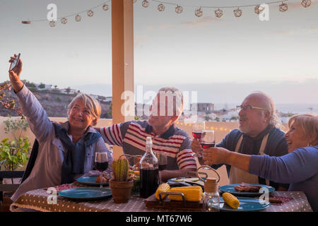 group of adults friends elderly retired having fun taking a picture like selfie all together during a dinner outdoor on the terrace rooftop. celebrate - Stock Photo