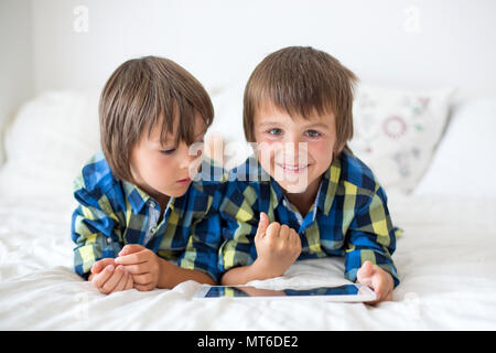 Two preschool children, boy brothers, playing at home in bed on tablet - Stock Photo