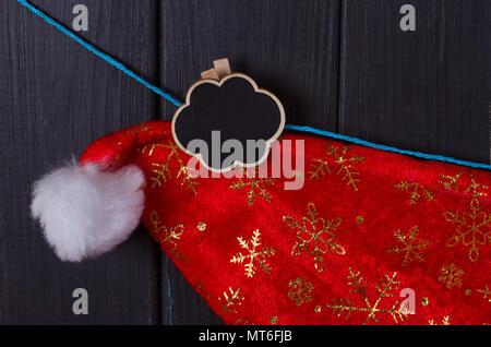 Santa Claus caps hang on a rope, an inscription Christmas - Stock Photo