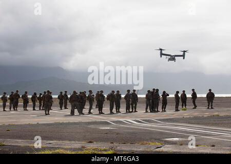 U.S. Marines with India Company, 3rd Battalion, 3rd Marine Regiment, standby for a MV-22 Osprey aircraft with Marine Medium Tiltrotor Squadron 268, prior to conducting a non-combatant evacuation operation (NEO) aboard Marine Corps Air Station Kaneohe Bay, July 25, 2017. During a NEO, Marines provide security, evacuate civilians, establish an intermediate support base and operate from naval support platforms at sea. Military personnel with Marine Aircraft Group 24 and 3rd Marines worked together in conducting a NEO which took place at three training areas across Oahu to include Marine Corps Tra - Stock Photo