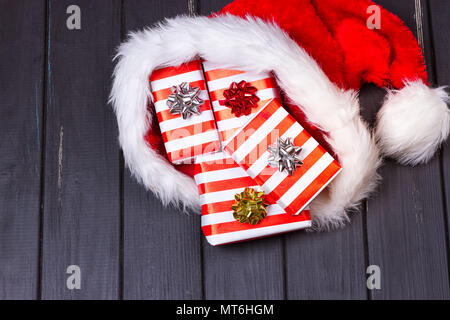 Christmas gifts in a Santa Claus hat on a black wooden background - Stock Photo