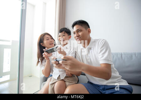 Asian family having fun playing computer console games together, Father and son have the handset controllers and the mother is cheering the players. - Stock Photo