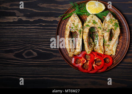 Fried fish in clay plate, on dark wooden background. - Stock Photo