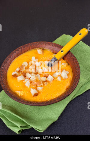 Pumpkin and carrot soup with cream and parsley on dark background - Stock Photo