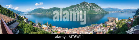 Lake Lugano. Panoramic view of Campione d'Italia, famous for its casino. In the background on the right the city of Lugano - Stock Photo
