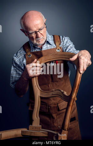 senior caucasian craftsman check unfinished chair studio shot - Stock Photo