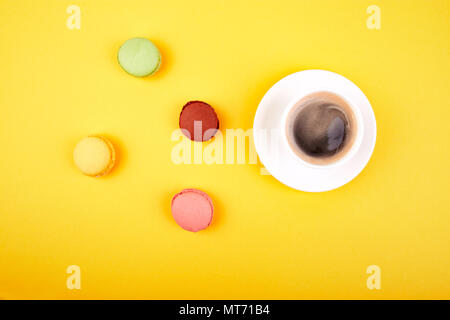 Sweet Dessert Macaron or macaroon with coffee on yellow background, colorful almond cookies, cakes. Good morning, breakfast. Spring. Flat lay. Copy sp - Stock Photo