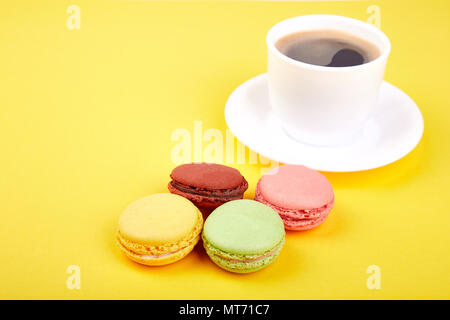 Sweet Dessert Macaron or macaroon with coffee on yellow background, colorful almond cookies, cakes. Good morning, breakfast. Spring. Copy space. Minim - Stock Photo