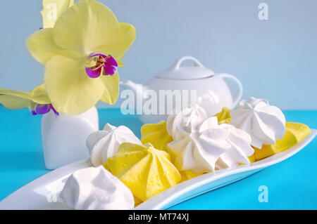 White and yellow meringue on blue background in tea serving with white kettle - Stock Photo