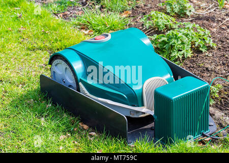 Green electric robotic Lawnmower charging on grass - Stock Photo
