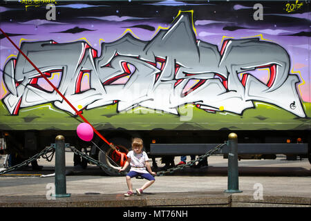 ZAGREB, CROATIA - MAY 19, 2018 : A little girl with balloon sitting on an iron chain fence of Mandusevac fountain in front of a truck painted with gra - Stock Photo