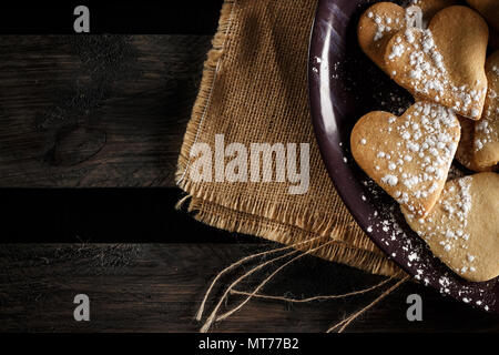 Delicious home-made heart-shaped cookies sprinkled with icing sugar on sackcloth and wooden boards. Horizontal image seen from above. - Stock Photo