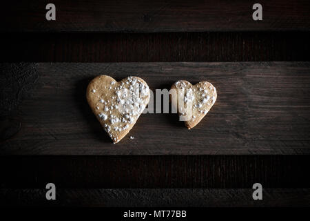 Two delicious home-made heart-shaped cookies sprinkled with icing sugar in a wooden board. Horizontal image seen from above. Concept of love in couple - Stock Photo