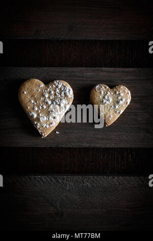 Two delicious home-made heart-shaped cookies sprinkled with icing sugar in a wooden board. Vertical image seen from above.Concept of love in couple. D - Stock Photo