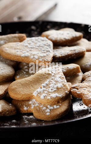 Delicious home-made heart-shaped cookies sprinkled with icing sugar on sackcloth and wooden boards. Vertical  image seen against backlight. - Stock Photo