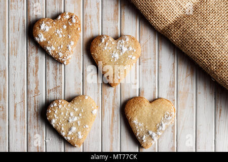 Delicious home-made heart-shaped cookies sprinkled with icing sugar in a wooden board. Horizontal image seen from above. - Stock Photo