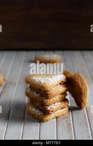 Delicious home-made heart-shaped cookies sprinkled with icing sugar in a wooden board. Vertical image Dark moody style. - Stock Photo