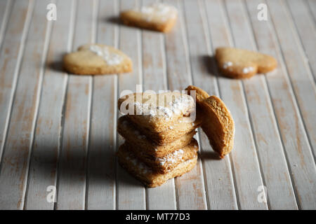 Delicious home-made heart-shaped cookies sprinkled with icing sugar in a wooden board. Horizontal image. Dark moody style. - Stock Photo