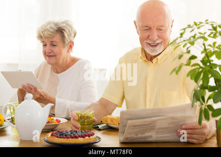 Happy elderly woman using a tablet and her husband reading a newspaper - Stock Photo