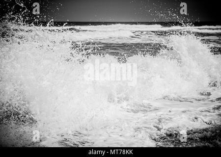 Crashing Choas as the waves break amongst the rocks in the sea - Stock Photo