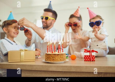 Birthday cake with candles and family out of focus. - Stock Photo