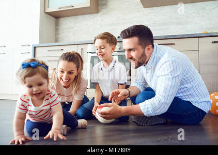 The family plays fun on the floor indoors - Stock Photo