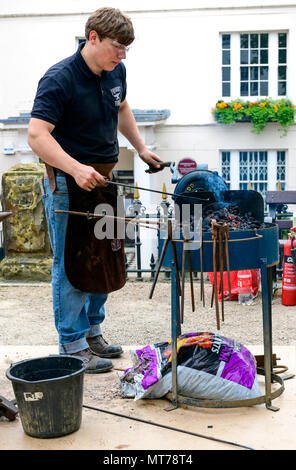 blacksmith working outdoors at the pantiles tunbridge wells heating iron in a fire - Stock Photo