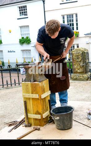 blacksmith working outdoors at the pantiles tunbridge wells making tradition iron items - Stock Photo