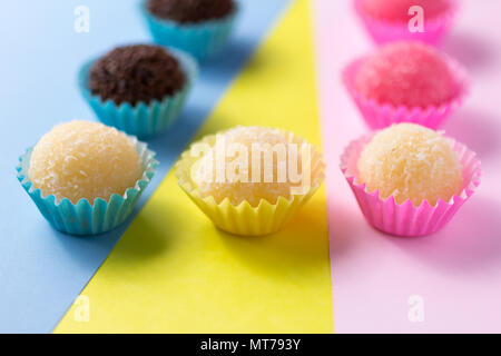 Beijinho is a handmade candy from Brazil. Made with condensed milk and coconut. Children brithday party sweet. Spread candy balls on colorful table. D - Stock Photo