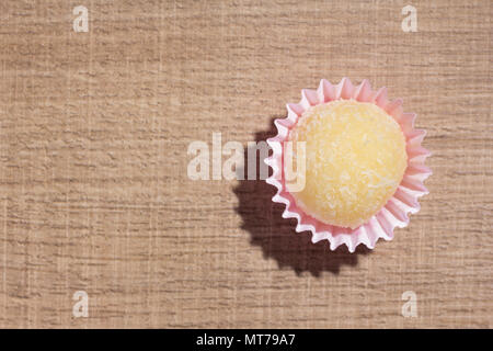 Beijinho is a handmade candy from Brazil. Made with condensed milk and coconut. Children brithday party sweet. Flat lay design of candy ball over wood - Stock Photo