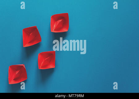 Set of red origami boats on blue paper background. Summer traveling concept. Top view. Toned - Stock Photo