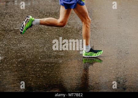 legs athlete runner running on wet from rain gray asphalt - Stock Photo