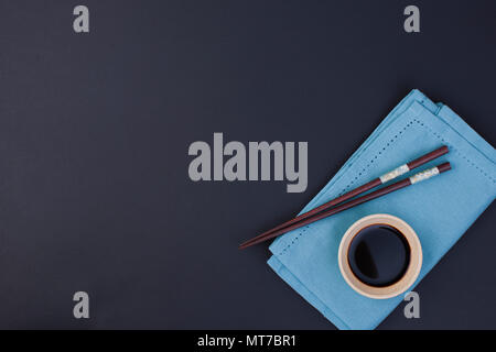 Soy sauce and chopsticks for Chinese food. Blue napkin and black background. Place for text - Stock Photo