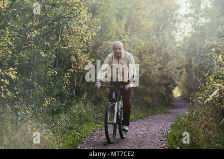 Portrait of man riding cycle in countryside. He is smiling a little