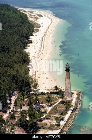 This aerial views shows how the historic 1825 lighthouse in Bill Baggs Cape Florida State Park looked in 1976 prior to its restoration when the original brickwork was covered with white stucco at the south end of Key Biscayne in Miami-Dade County, Florida, USA. A bright navigational beacon atop the 95-foot-tall (29 meters) landmark lighthouse was relit in 1996 in celebration of Miami's centennial. In the background is a stretch of beautiful white sand beach that is a main attraction for sunbathing residents and visitors to Miami. Historical photo. - Stock Photo