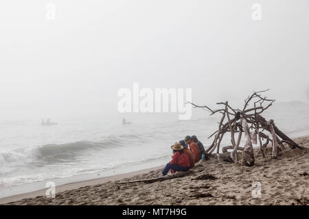 Family of four sitting by the ocean, California. - Stock Photo