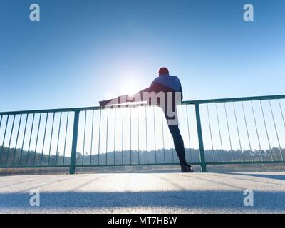 Sportsman doing stretching at handrail in the park. Silhouette against sun, sports concept. - Stock Photo