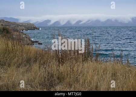 Clouds cascade down the hills surrounding Lake Sevan in Armenia on a very windy day in autumn - Stock Photo