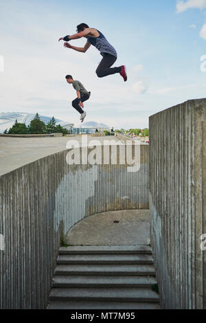 Teenage free runners jumping off concrete structure and doing parkour - Stock Photo