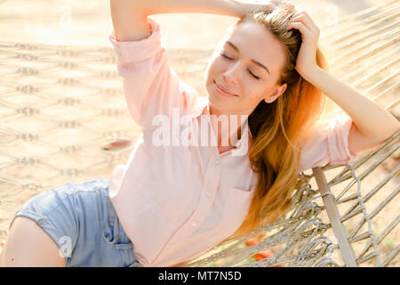 Close up young woman lying in white wicker hammock on sand, wearing jeans shorts. - Stock Photo