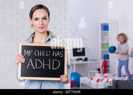 Mother of child with ADHD holding small blackboard with text - Stock Photo