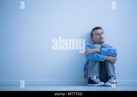 Lonely autistic child sitting on a floor in a room - Stock Photo