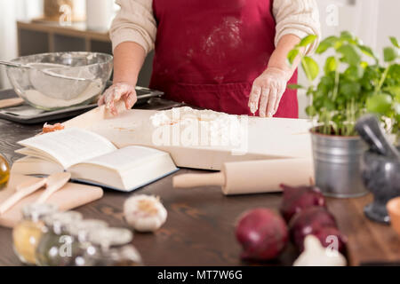 Woman preparing a dough on a table in modern kitchen - Stock Photo
