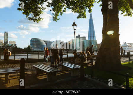 people walk on the embankment near Tower Millennium Pier. Shard and City Hall - Stock Photo