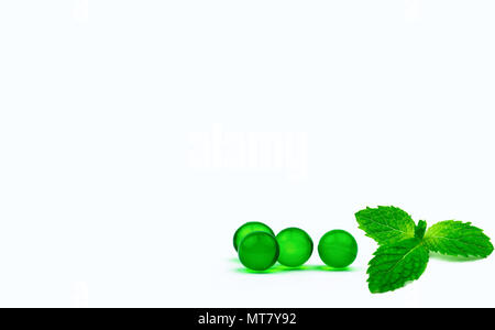 Green round soft capsule pills and mint leaves isolated on white background with copy space. Ayurvedic medicine for indigestion, gas and acidity. Herb - Stock Photo