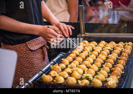 Takoyaki being prepared at a foodstall in Osaka, Japan. - Stock Photo