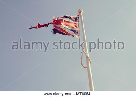 A weathered Union Jack flag flying in the breeze on the bank of the River Thames in London, England, Great Britain - Stock Photo