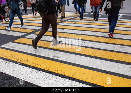 people cross the road on a pedestrian crossing - Stock Photo