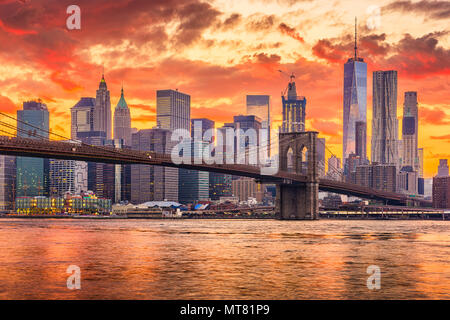 New York, New York, USA skyline of Manhattan on the East River with Brooklyn Bridge after sunset. - Stock Photo