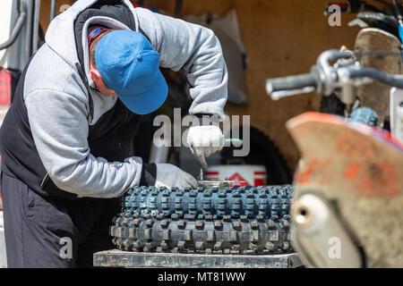 mechanic fixing motocycle wheel - Stock Photo